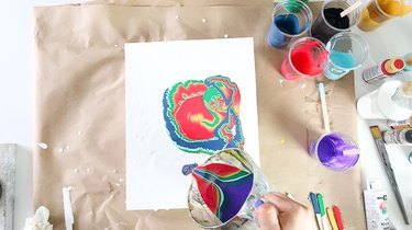 Pouring paint onto canvas from cup.