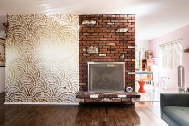 red-toned brown hardwood floor colors in living room with brick wall and wallpaper