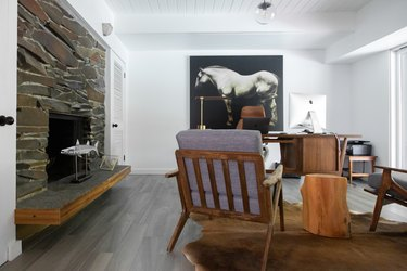 gray hardwood floor colors in living room with stone fireplace and cowhide rug