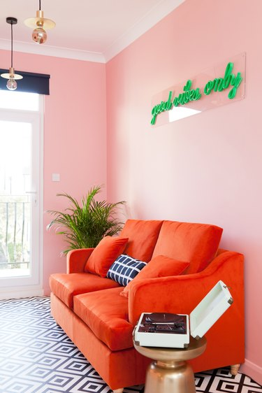 pink room living room with red sofa and green neon light