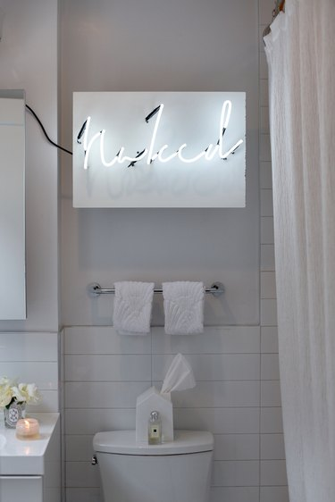 neon sign in all white bathroom