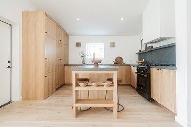 light hardwood floor colors in kitchen with light wood cabinets and black stone backsplash