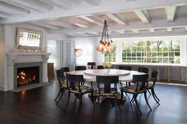 dark brown hardwood floor colors in dining room with fireplace and white ceiling beams