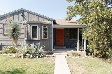gray house with white and wood exterior window trim and red front door