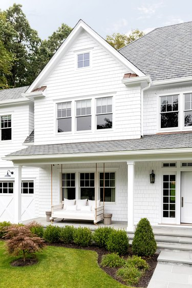 White clad house with white exterior window trim and porch swing
