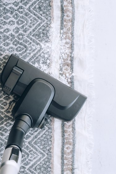Vacuum cleaning rug sprinkled with carpet cleaner.
