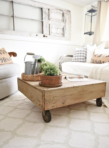 DIY rustic coffee table displaying a wood pallet and wheels in farmhouse living room