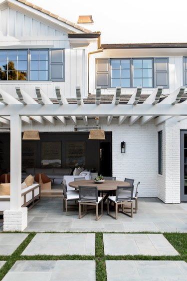 White house with gray exterior window trim and outdoor seating area