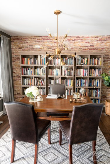 Rustic office with brick wall and wood table with leather chairs