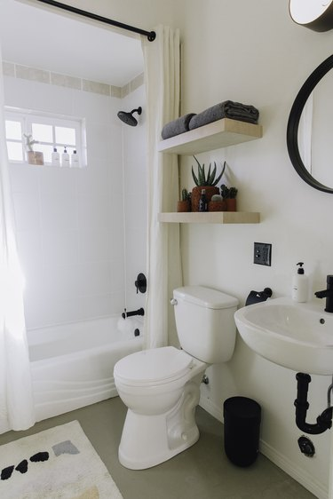 wall-hung sink, white toilet, open shelving over the toilet, round mirror with black trim, white tub/shower combination, white shower curtain