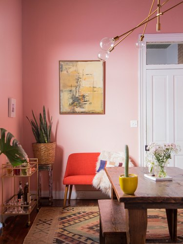 pink dining room with red settee and brass chandelier