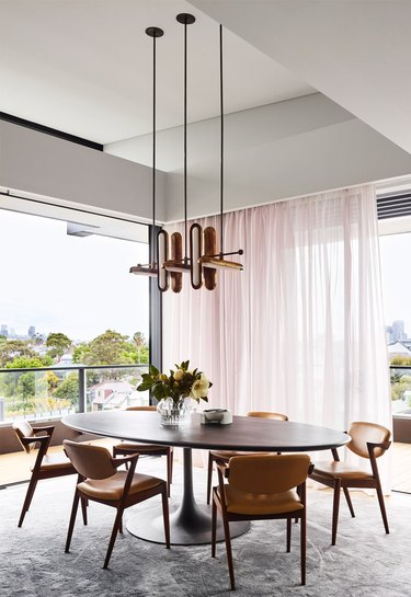 pink dining room with blush sheer drapery and oval table