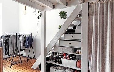 bedroom storage idea under stairs hidden by IKEA curtains