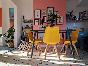 pink dining room idea with one accent wall and yellow chairs