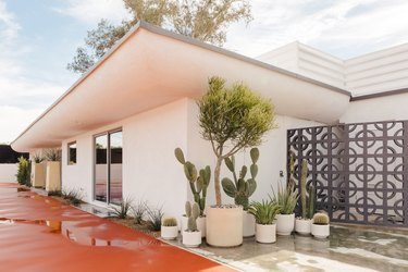 midcentury palm springs tennis club exterior with potted cactuses