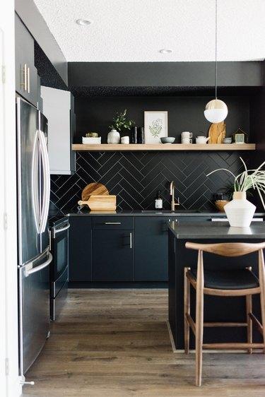 Modern kitchen idea with black herringbone backsplash