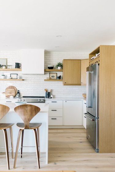 modern kitchen idea with white backsplash and wood cabinets with white countertop