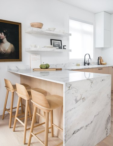 modern kitchen idea with marble waterfall countertop and light-colored woods
