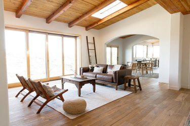 rustic decor with hardwood floors, exposed wood ceiling beams, and skylight in living room