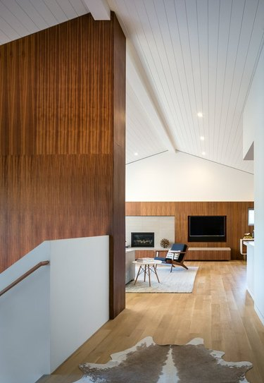 minimal midcentury modern living room and staircase with dark wood paneling