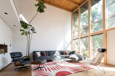 midcentury living room with high, open-beamed ceilings and large wall of windows