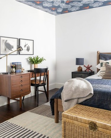 bedroom office idea with dark wood midcentury style desk in a white room with blue, red, and white wallpaper on the ceiling