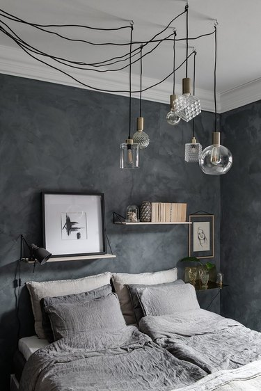 greenish gray paint colors in bedroom with gray linen sheets and hanging light fixture
