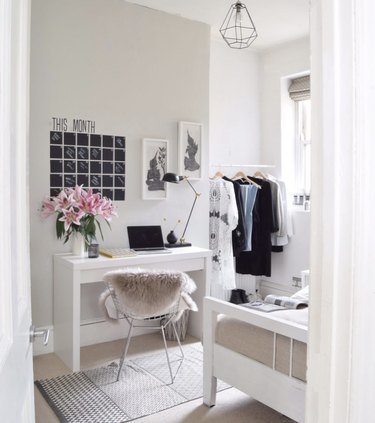 bedroom office idea with white desk with a chalkboard vinyl wall calendar on a tan wall