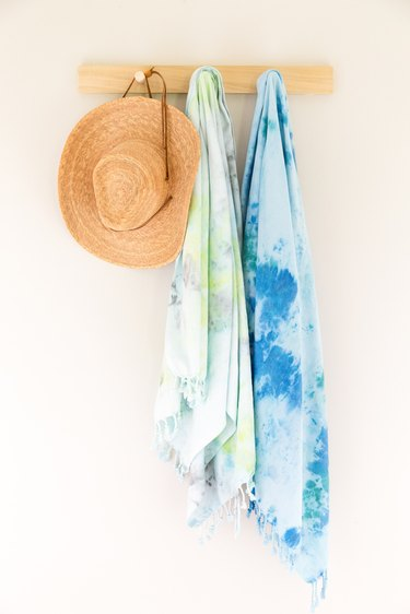 Ice dye beach towels hanging from a peg hook