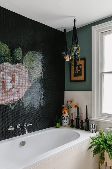 white bathtub with black wall with rose mosaic, hanging plants from black macrame, white tile on the walls, plants surrounding the bathtub