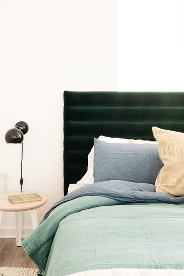 channel tufted headboard in bedroom with black wallsconces and side table