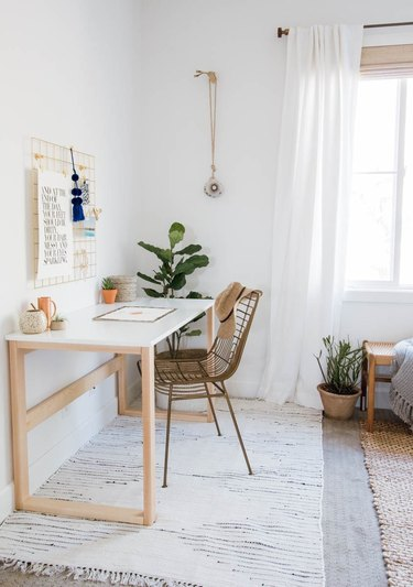 bedroom office idea with light wood and white desk against a white wall in a mostly white bedroom