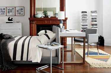 bedroom office idea with gray upholstered bed with black and white stripped bedding. A desk sits at the headboard of the bed.
