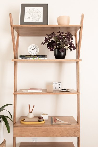 wooden shelving unit in bedroom styled with decorative accents
