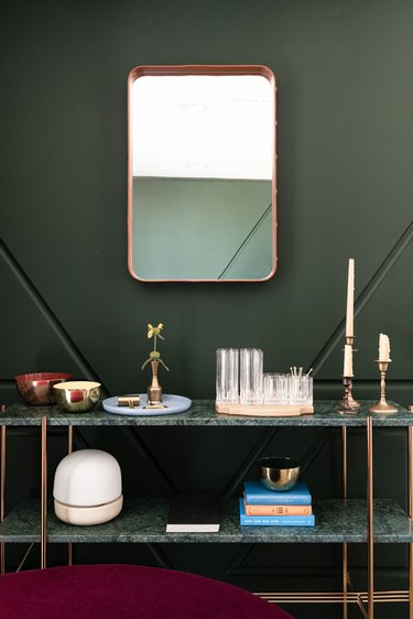 Gubi Adnet Rectangulaire Mirror hung on green accent wall above console table