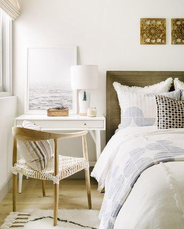 nightstand slash desk in bedroom between bed and window