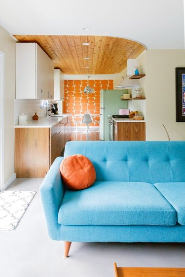 midcentury robin's-egg blue couch with mint smeg fridge in a galley kitchen