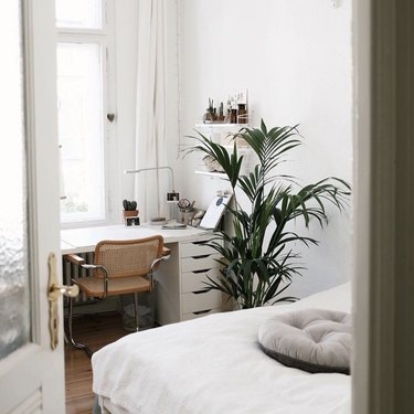 bedroom office idea with white desk against a window with a mid-century cane chair and a bed with white bedding in a white bedroom