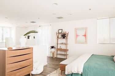 four drawer dresser in bedroom with bed bench and shelving unit