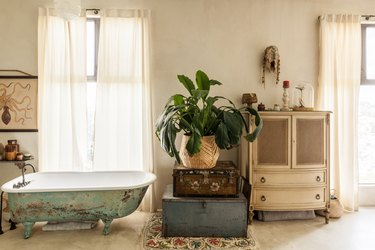 freestanding cast iron tub with vintage distress, trunks stacked on top of each other with a plant on top, a white vintage cabinet is placed between two windows