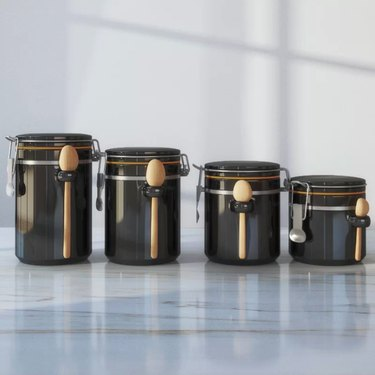 Four black kitchen canisters in varying sizes