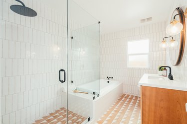 glass walk-in shower, orange patterned floor tile, white vertical subway wall tile, wood vanity with white countertop, round mirror, bathtub
