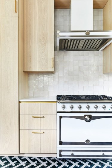 light wood cabinets with patterned tile floor and textured backsplash and brass hardware