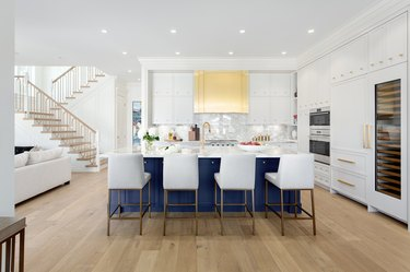 white kitchen with blue island and gold vent