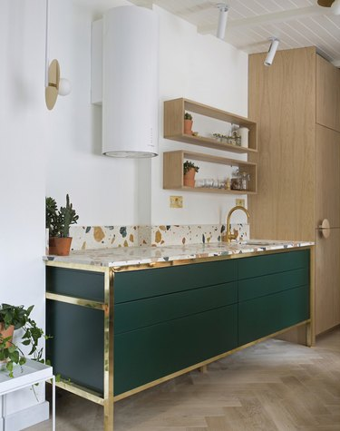 modern kitchen with green cabinets with brass detailing and terrazzo countertop