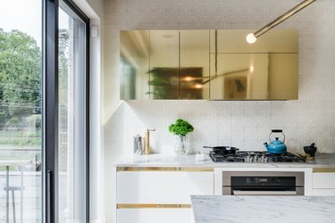 White kitchen with brass upper cabinets and white lower cabinets with brass reveal