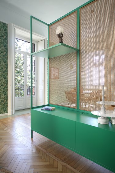 cane cabinet with green shelves