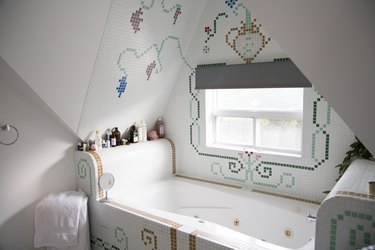 jetted tub with decorative tile surrounding it, bath products on the tub ledge