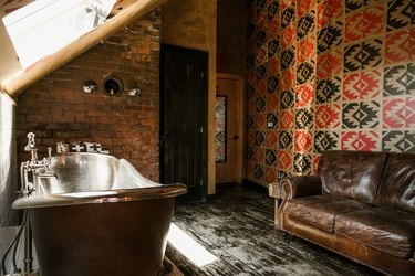freestanding copper bathtub, distressed black wood floors, exposed brick walls, patterned red and black walls, leather couch