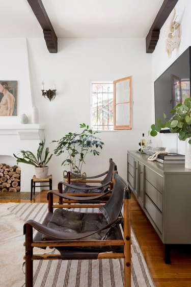 simple green living room idea with credenza for storage and leather lounge chairs with exposed ceiling beams